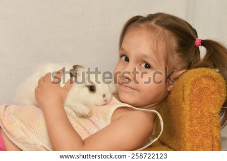 Portrait of a  girl with a rabbit at home - stock photo