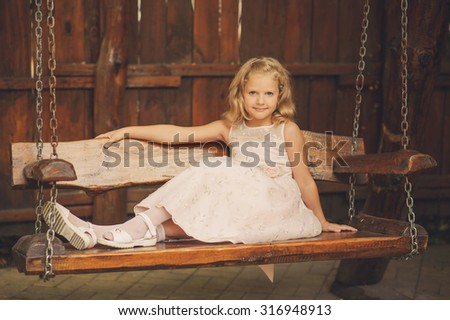 Portrait of a girl with blond hair on wooden swing. Happy child, cute little baby or toddler girl with blonde curly hair swinging on a wooden swing outdoors in a park. - stock photo