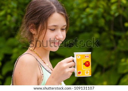 Portrait of a girl with cup of tea - stock photo