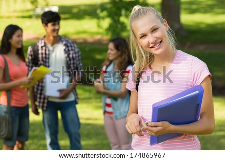 Portrait of a girl with happy college friends in background at the campus - stock photo