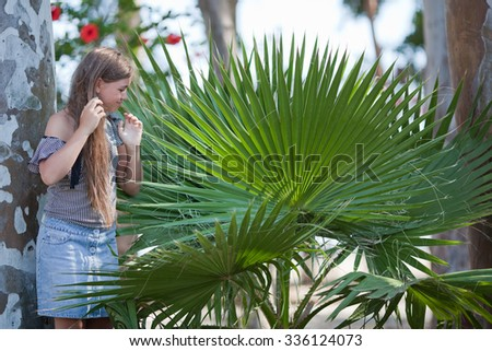 Portrait of a girl with  palm (livistonia) - stock photo