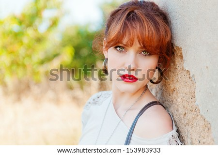 portrait of a girl with red hair, red lips and green eyes against the wall in the background green trees, look at the camera, horizontal frame - stock photo