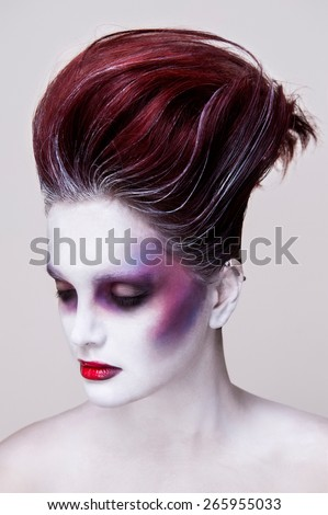 Portrait of a girl with red hair wearing an undead makeup with purple cheeks, red lips and white skin. Her eyes are closed - stock photo