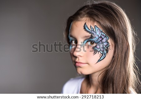 Portrait of a girl with the picture painted on her face - stock photo