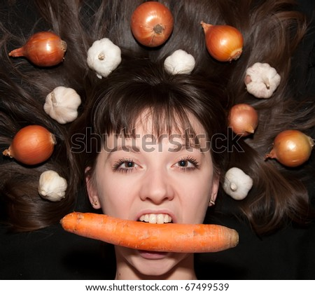 portrait of a girl with vegetables in her hair - stock photo