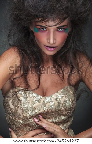 Portrait of a glamorous fashion woman posing with her hands around her waist, looking at the camera - stock photo