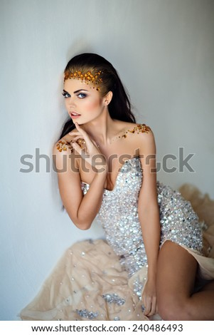 Portrait of a glamorous very beautiful girl brunette with sequins on the face and in a brilliant dress , sitting on the floor - stock photo