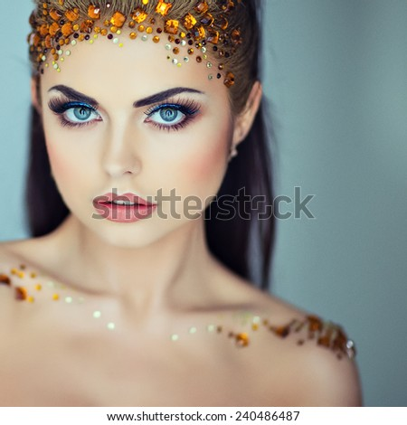 Portrait of a glamorous very beautiful girl brunette with sequins on the face, close up - stock photo