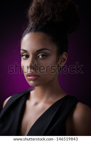 Portrait of a glamorous young African woman against a purple background. - stock photo
