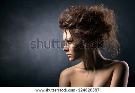 portrait of a glamorous young woman on dark background - stock photo