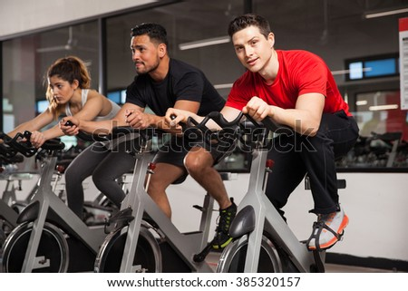 Portrait of a good looking Hispanic young man doing some spinning at a gym and making eye contact - stock photo