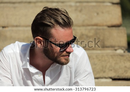 Portrait of a good looking man in his 20s, wearing a white shirt with dark sunglasses, sitting down outside on a set of steps on a sunny summer day. - stock photo