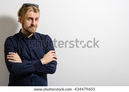 Portrait of a good looking smiling young man with sunglasses with his arms crossed - stock photo