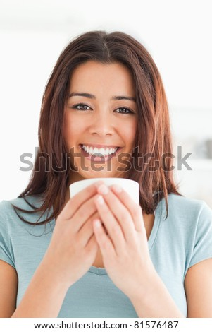 Portrait of a good looking woman enjoying a cup of coffee in the kitchen - stock photo