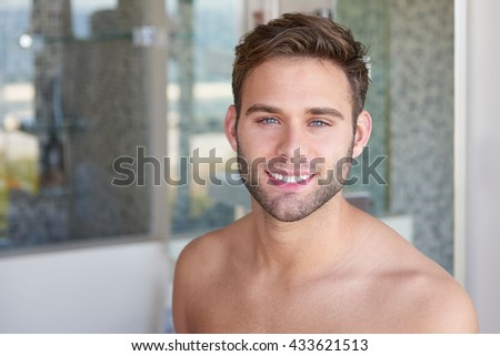 Portrait of a gorgeous blue-eyed young man, standing in a modern bathroom, shirtless and looking healthy and fresh while smiling at the camera  - stock photo