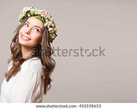 Portrait of a gorgeous brunette woman wearing spring flower wreath. - stock photo