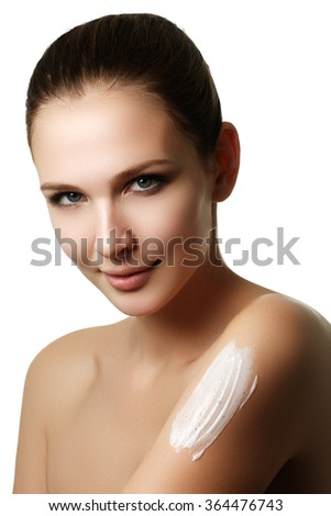 Portrait of a gorgeous brunette woman with smooth and healthy skin. Applying moisturizer cream. Smiling woman looking down applying body cream to her bare shoulder in a health and beauty concept - stock photo