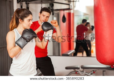 Portrait of a gorgeous Hispanic brunette practicing boxing with her personal trainer at the gym - stock photo