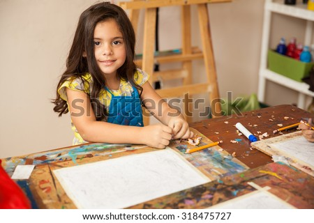 Portrait of a gorgeous little girl with an apron drawing something for art class - stock photo
