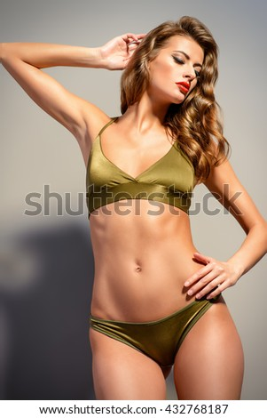 Portrait of a gorgeous sexual young woman in bikini and with bright make-up and beautiful wavy hair. Beauty, fashion. Cosmetics, make-up. Underwear and bikini fashion. - stock photo