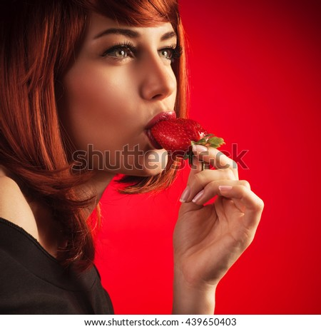 Portrait of a gorgeous sexy woman temptingly biting fresh tasty sweet strawberry, over red background - stock photo