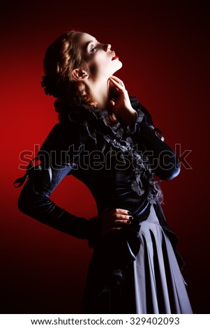 Portrait of a gorgeous vampire woman in black medieval dress over dark bloody  background. Halloween.  - stock photo