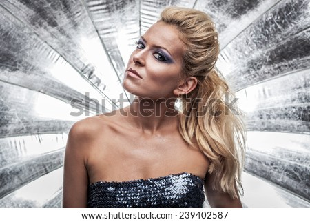 Portrait of a gorgeous woman against silver background - stock photo