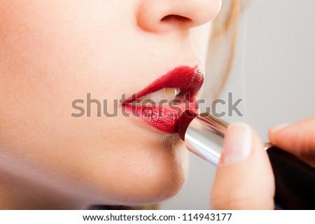 Portrait of a gorgeous woman applying lipstick - stock photo