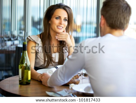 Portrait of a gorgeous woman holding hands with her boyfriend at a fancy restaurant - stock photo