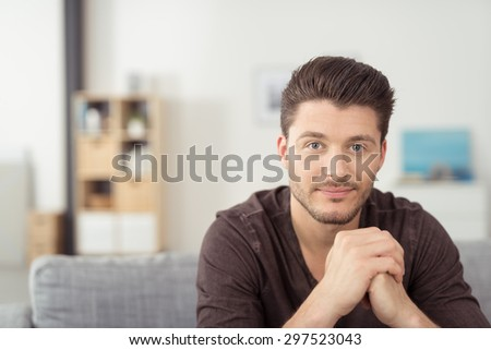 Portrait of a Gorgeous Young Bearded Guy Sitting on the Couch at the Living Room and Staring at the Camera - stock photo