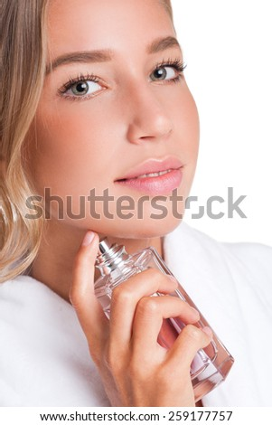Portrait of a gorgeous young blond woman enjoying perfume. - stock photo