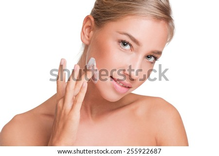 Portrait of a gorgeous young blond woman using body lotion. - stock photo