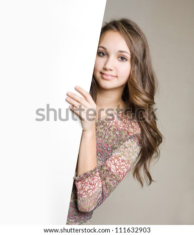 Portrait of a gorgeous young brunette teen with blank white sign. - stock photo