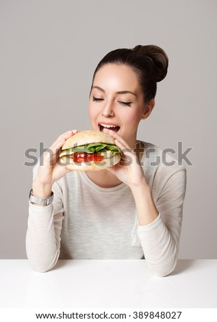 Portrait of a gorgeous young brunette woman showing diet food choices. - stock photo