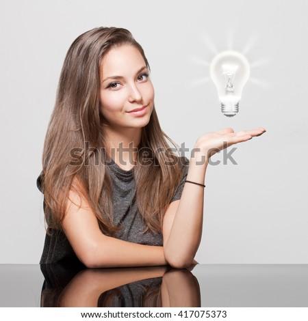 Portrait of a gorgeous young brunette woman with light bulb idea symbol. - stock photo