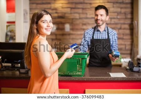 Portrait of a gorgeous young Hispanic brunette using a credit card to pay for her groceries at a store - stock photo