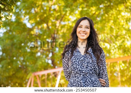 Portrait of a gorgeous young Hispanic woman hanging out at a park and smiling - stock photo