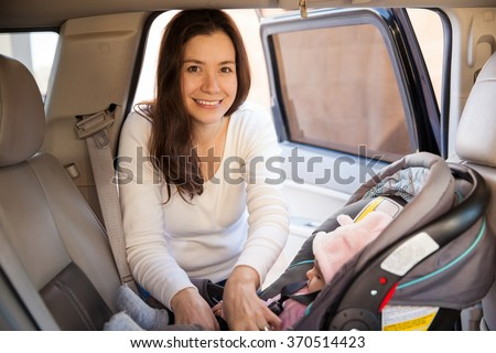 Portrait of a gorgeous young mother securing her baby on a child seat before driving - stock photo