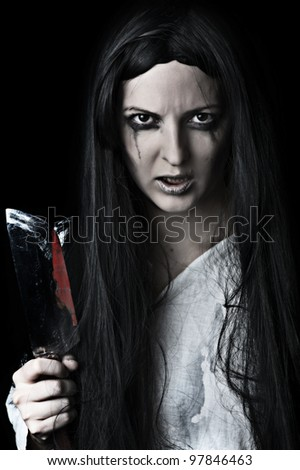 Portrait of a gory and scary zombie woman on black background with bloody knife - stock photo