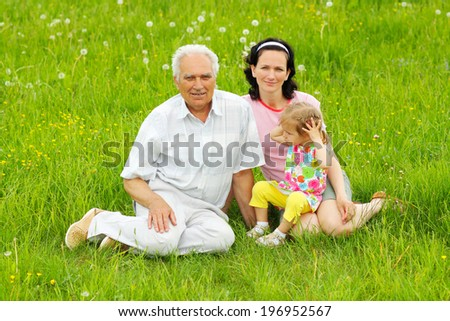 portrait of a grandfather, daughter and granddaughter on a green meadow - stock photo