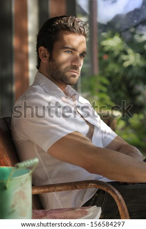 Portrait of a great looking masculine man relaxing on a front porch  - stock photo
