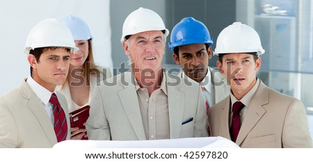 Portrait of a group of architect in a building site - stock photo