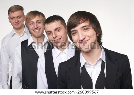 Portrait of a group of young men standing in line. Shallow depth of field, focus on the front male. - stock photo