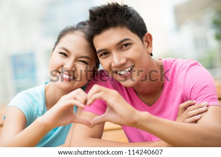 Portrait of a guy and a girl forming a heart shape with their hands - stock photo
