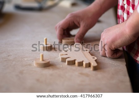 portrait of a hands carpenter planing on composition of  wood element wheel dinosaur toy  at work in the workshop / cabinetmaker's hands using sandpaper on a piece of wood - stock photo