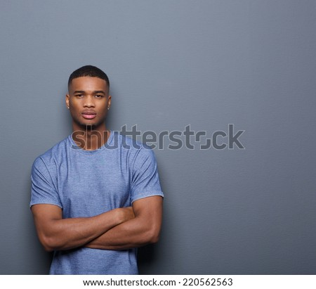 Portrait of a handsome african american man posing with arms crossed on gray background - stock photo