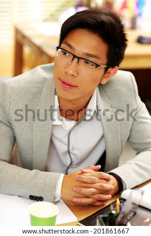 Portrait of a handsome asian man in glasses at office - stock photo