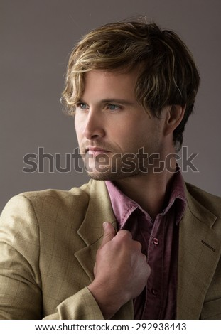 Portrait of a handsome blonde caucasian man wearing a pale purple button shirt with olive beige formal suit jacket. - stock photo