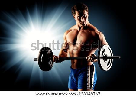 Portrait of a handsome bodybuilder posing over black background. - stock photo