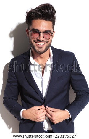 Portrait of a handsome business man unbuttoning his jacket with a smile on his face, looking at the camera - stock photo